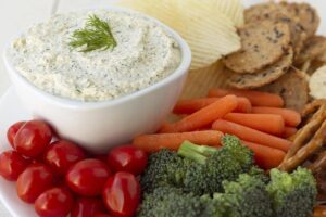 Vegan dill dip next to chips, crackers, and raw vegetables.