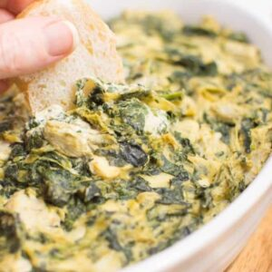 Vegan spinach artichoke dip with a piece of bread dipped into it.