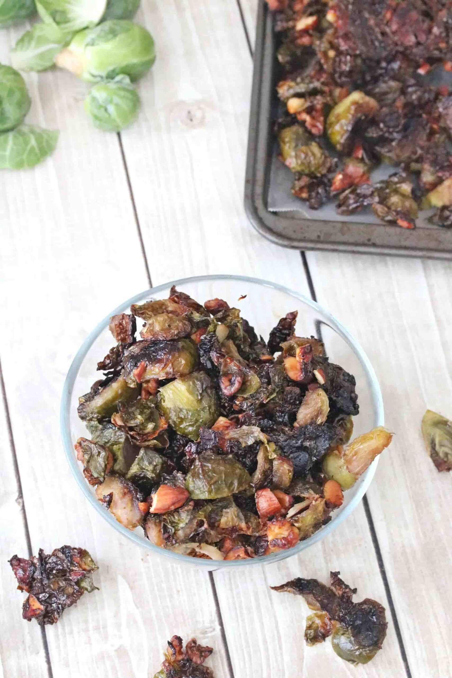 A bowl of brussels sprouts next to a pan of them.
