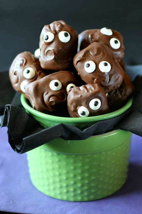 A container of chocolate candies with candy eyes.