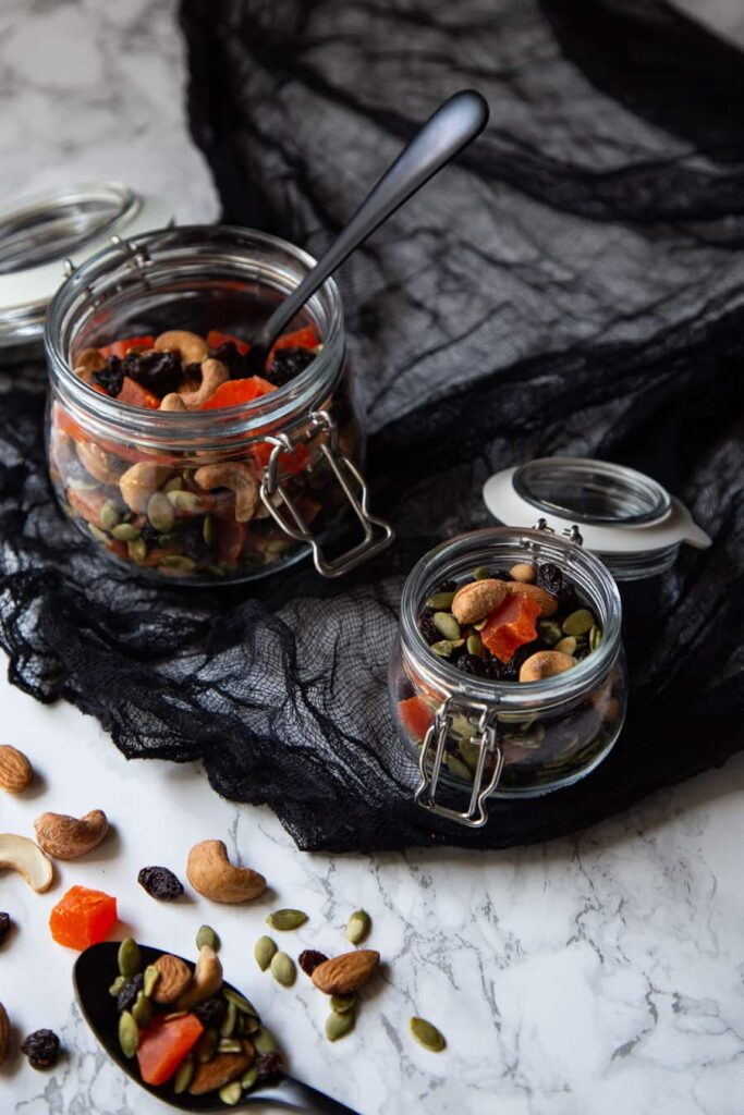 Two glass containers of Halloween-colored trail mix.