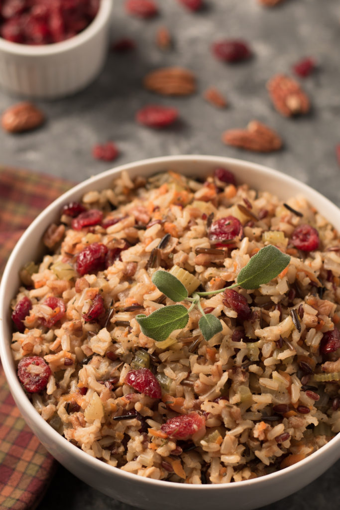 A bowl of wild rice pilaf with pecans and cranberries.