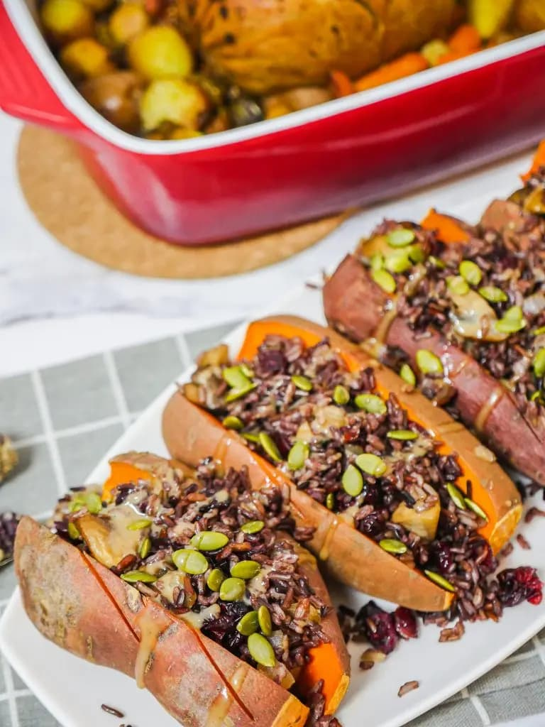 A row of sweet potatoes stuffed with rice, cranberries, and more.