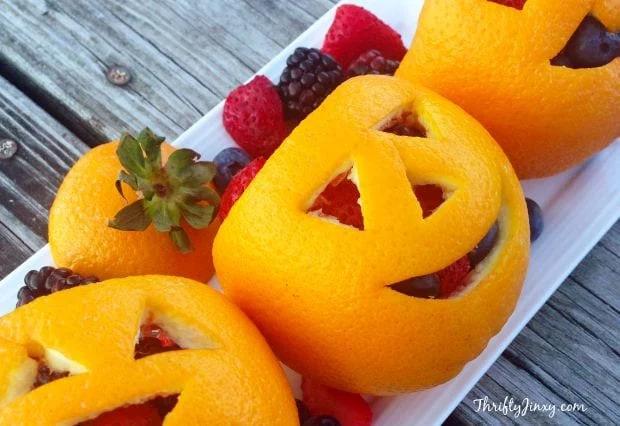 Orange peels cut like jack-o-lanterns with fruit inside of them.