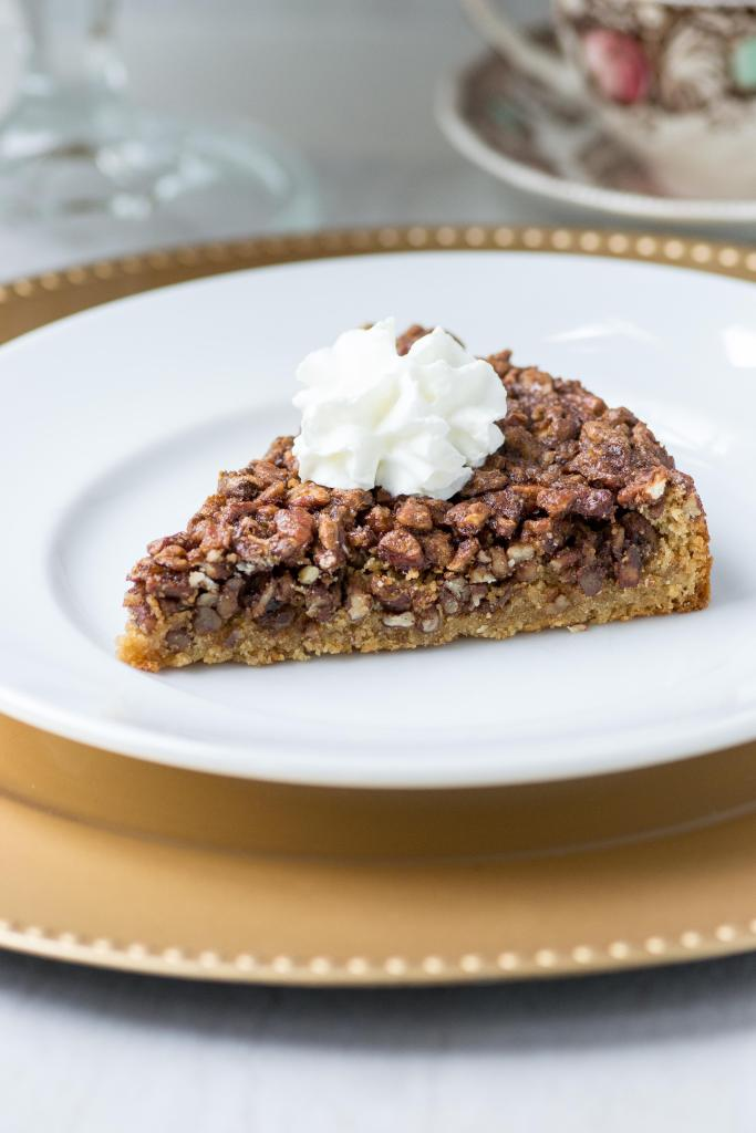 A slice of pecan blondie pie with whipped cream on top.