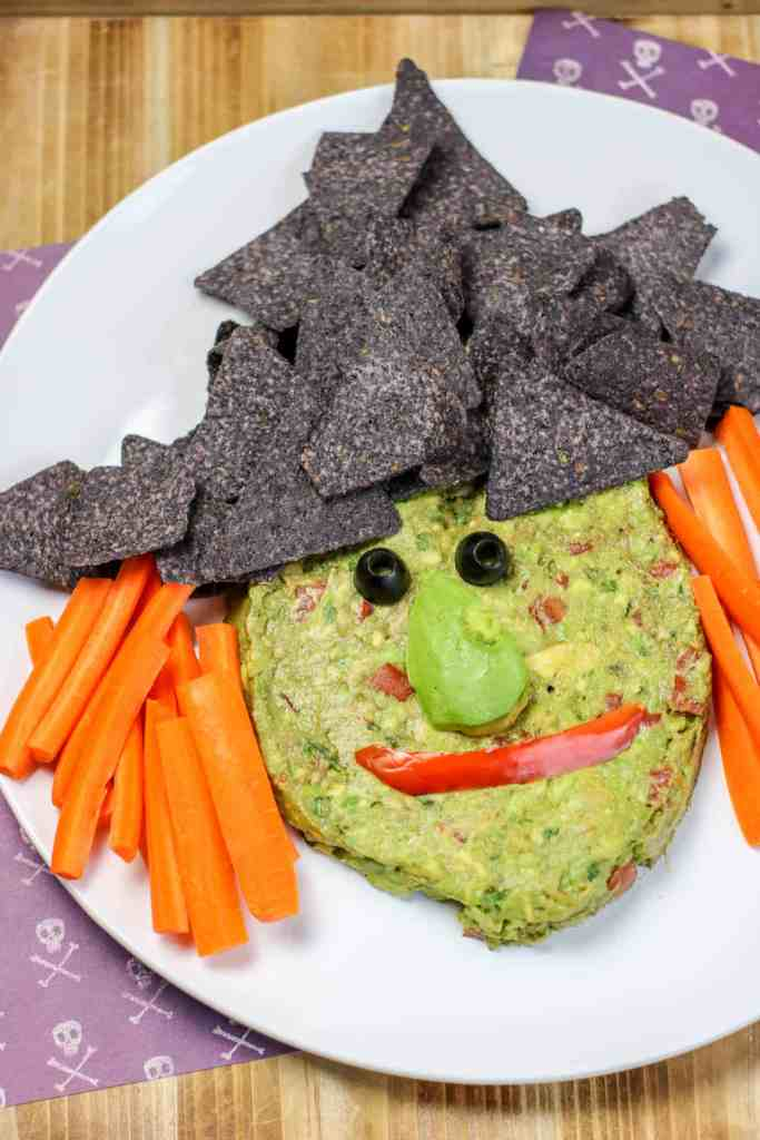 Guacamole, chips, and veggies in the shape of a witch face.