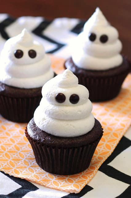 Chocolate cupcakes with white frosting and candy eyes.