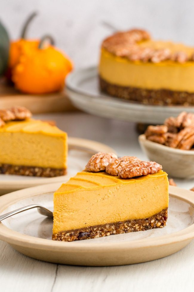 A slice of pumpkin cheese cake with more slices seen in the background.