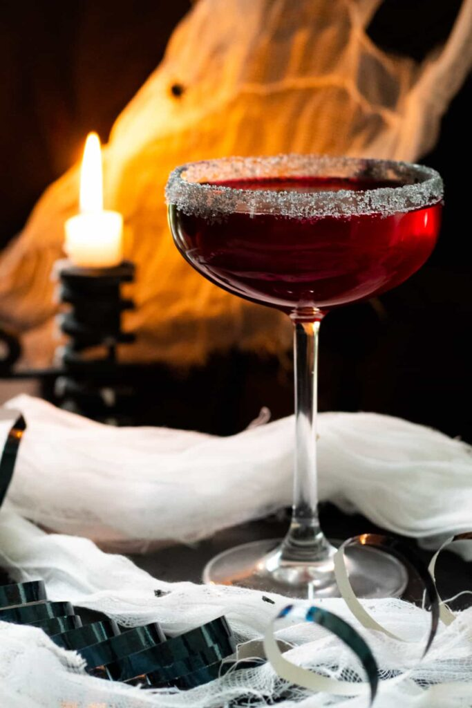 A red vampire-themed mocktail in a wine glass.