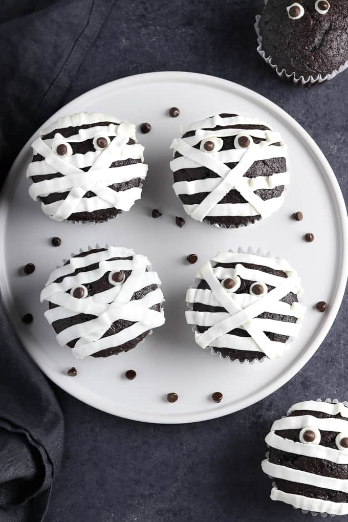 A plate of chocolate cupcakes with white icing to make them look like mummies.